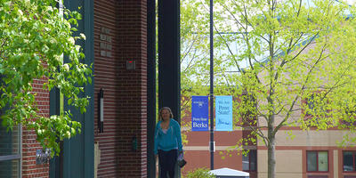 A female student walks through the archway at the Woods residence halls.