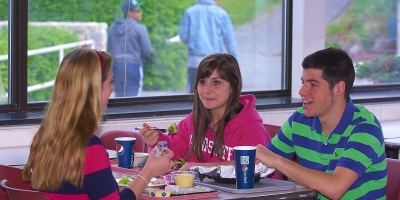 Three students have lunch together in the Tully's dining room.
