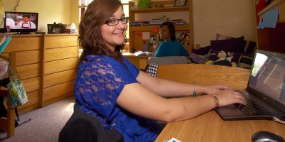 A female students sits at a desk in a residence hall room.