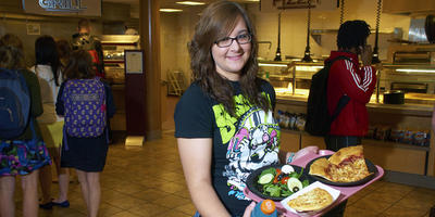 A female student standing in Tully's holding a tray with a slice of pizza and a small salad on it.