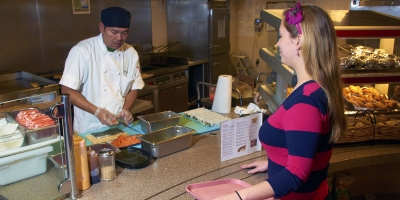 A chef prepares sushi for a student at Tulley's.
