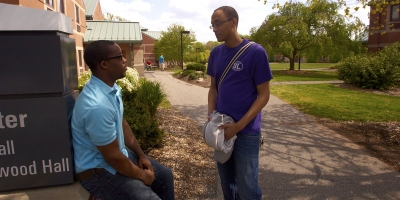 Two male students talk outside on campus