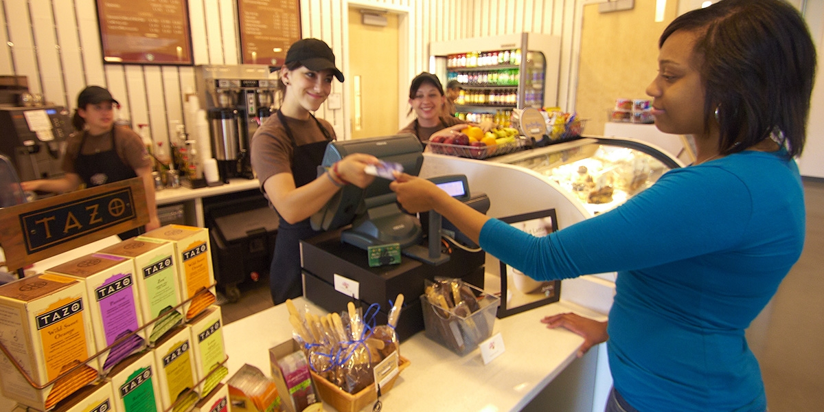Student cashier returns an id plus card to a student after processing payment for a coffee