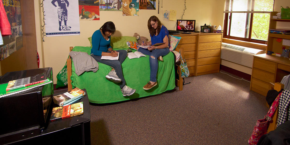 Two female students sit on a bed and study in a residence hall room