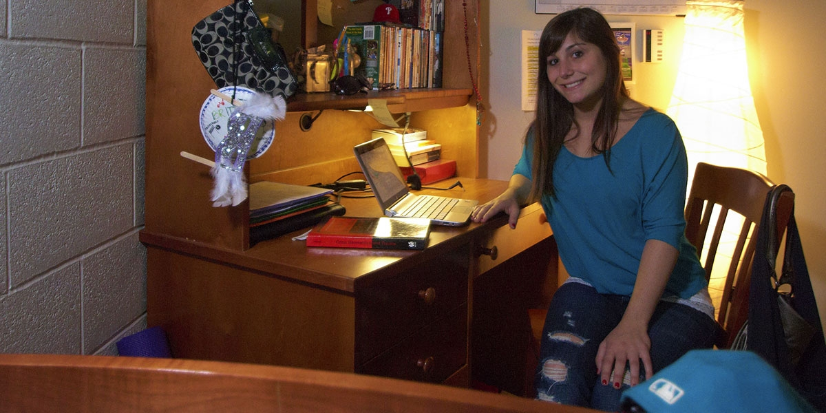 Female student in residence hall at desk